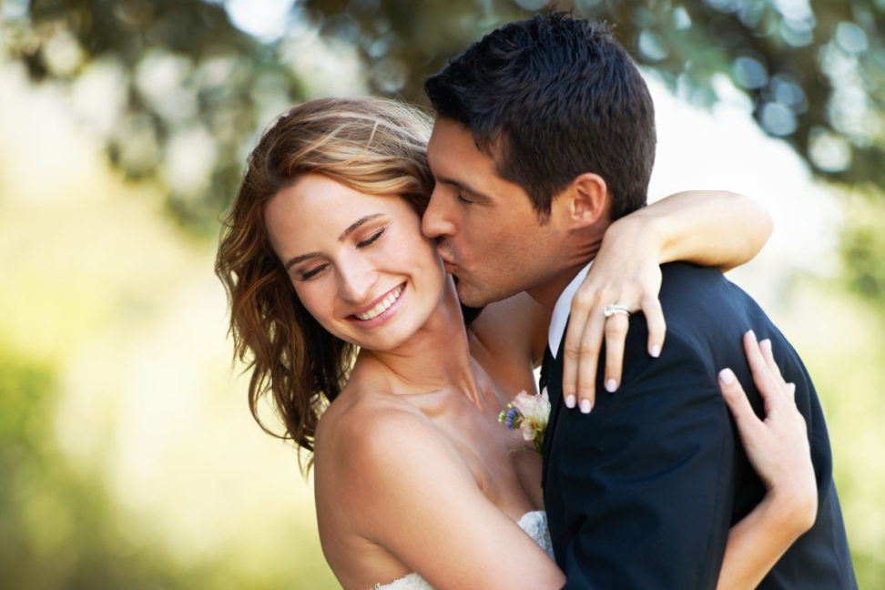 A happy groom kissing his bride on the cheek in a loving embrace